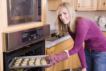 Woman putting cookies in oven