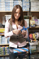 Young shop assistant wrapping a gift