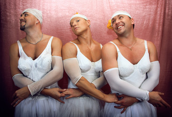 Three strong men in suits of ballerinas. Ñomic photo on a pink b