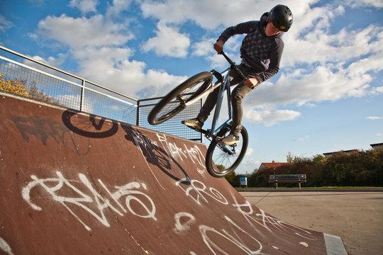Jugendlicher springt an der Halfpipe mit dem Dirtbike