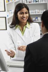 Indian female pharmacist talking to customer