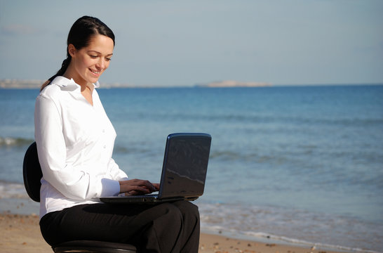 Business woman working from the beach