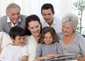 Family sitting on sofa reading a book