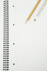 Close up of a  Blank white lined Notepad with a pen and pencil o