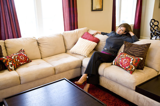 Mature woman relaxing on couch in elegant modern living room