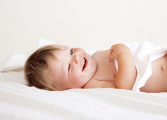 baby lying on white sheet smiling