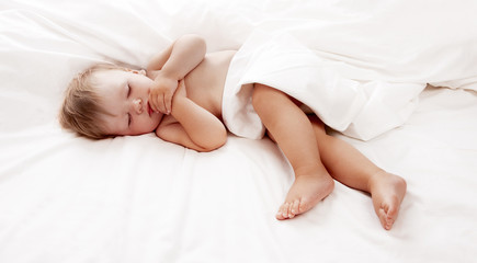Baby lying in white sheets
