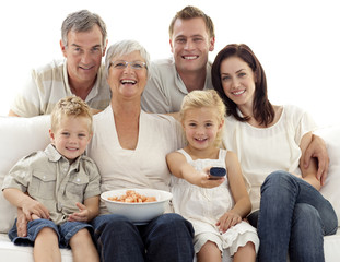 Family watching television and eating chips at home