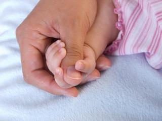 Babyhand umfasst den Daumen von Mutters Hand
