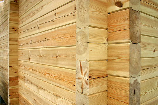 Wall and corner of planed pine log cabin