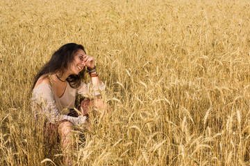 Attractive girl sitting in golden wheat