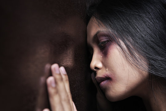 Injured woman leaning sadly on wooden wall