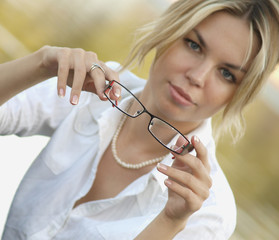 A blond with spectacles in her hands.