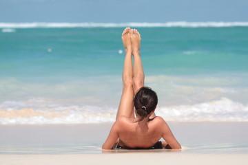 Obraz Kobieta leżąca na plaży na plecach z uniesionymi nogami - fototapety do salonu