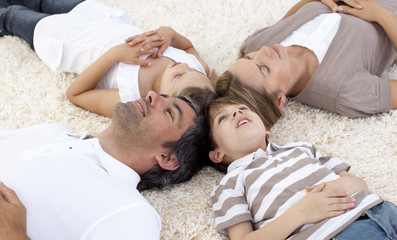 Family lying on floor at home with heads together