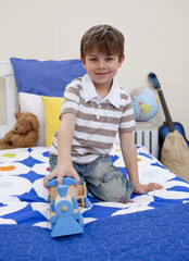 Little boy playing with a train in his bedroom