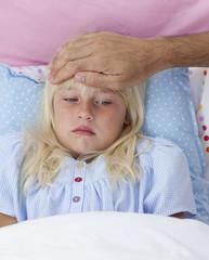 Sick girl in bed having flu