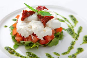 Dish with tomatoes, salad ruccola and cheese a mozzarella