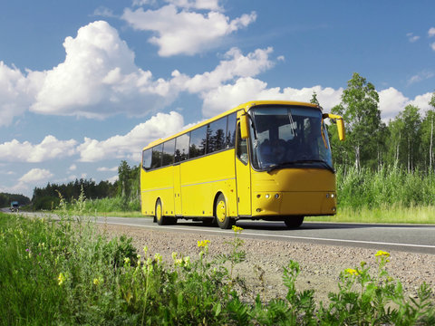yellow tourist bus on highway and rural landscape