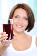beautiful young woman holds a glass of cherry juice