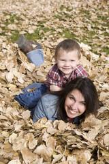 Boy on mom back in leaves