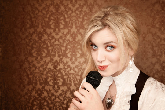 Pretty young singer or comedian with microphone