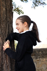 Portrait the girl, teenager in a jacket and jeans near a tree.