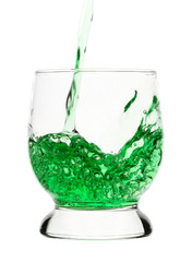 Green drink is being poured into glass