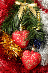 christmas hearts hanging on fir branch on tinsel background