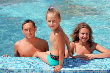 Happy family with little girl bathe in pool, daughter sits near