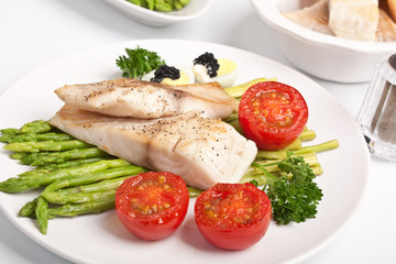 healthy fish fillet with asparagus and tomatoes