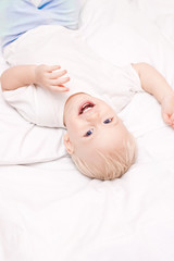 Cute little boy lying on the bed laughing