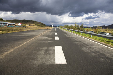 road goes into distance with a coming storm