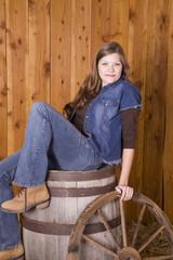 Woman sitting on barrel with wagon wheel