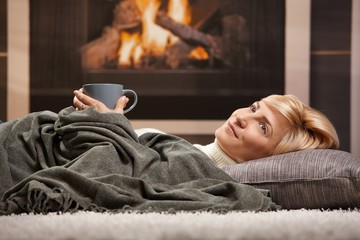 Woman resting beside fireplace