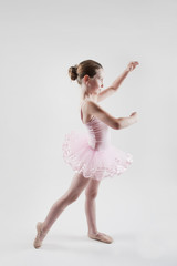 little girl practicing ballet in pink tutu