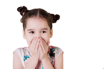 Laughing little girl covering her mouth with her hands