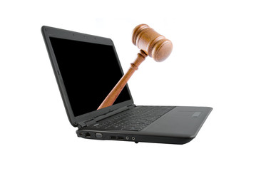 Modern laptop with judge's gavel isolated on white background