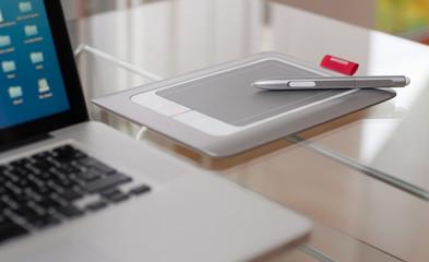 Grafiktablet mit Stift neben Laptop