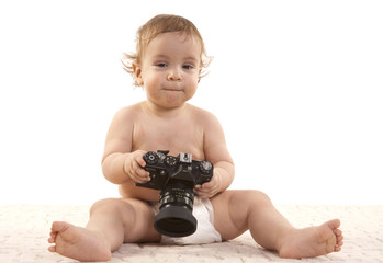 The little boy plays a camera a white background