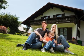 Familie sitzt vor ihrem Eigenheim