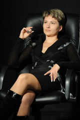 Portrait of the business woman in a leather armchair