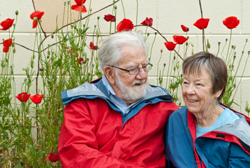 Eighty year old couple in red and blue raincoats near poppies