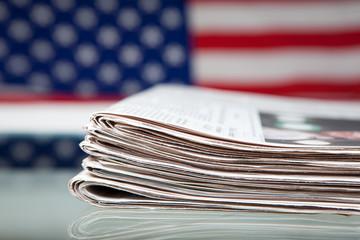 Stapel Zeitungen mit Flagge der USA dahinter auf Glastisch