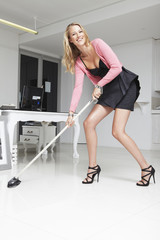 Young woman cleaning office