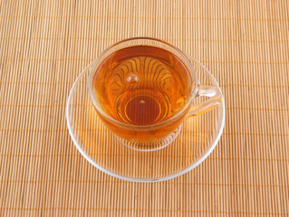 Glass cup of tea on wooden background