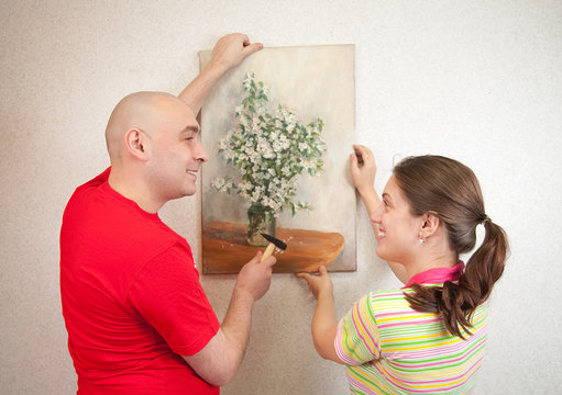 couple hanging up an art picture on their wall