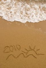 Year 2010 written on the sand