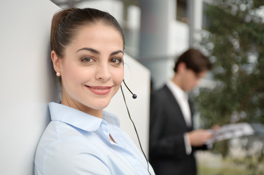 junge frau in büro telefoniert mit headset mit kunden
