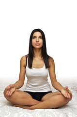 Young beautiful girl sitting in pose of meditation